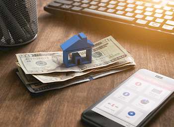 Small plastic model of a house on a stack of twenty dollar bills beside a phone with an online banking app open